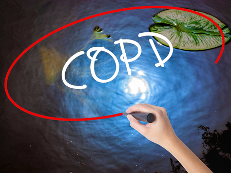 Woman Hand Writing COPD with marker over transparent board. Isolated on nature. Business concept. Stock Photo Stock Photo