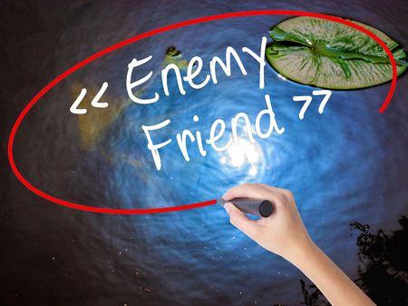 duplicitous: Woman Hand Writing Enemy - Friend with marker over transparent board. Isolated on nature. Business concept. Stock Photo