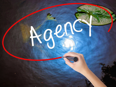 adwords: Woman Hand Writing Agency with marker over transparent board. Isolated on nature. Business concept. Stock Photo Stock Photo