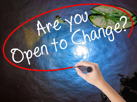 Woman Hand Writing Are you Open to Change? with marker over transparent board. Isolated on nature. Business concept. Stock Photo