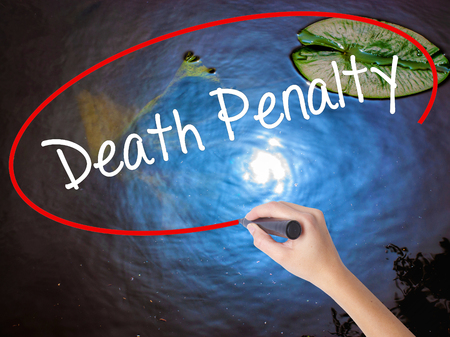 or electrocution: Woman Hand Writing Death Penalty with marker over transparent board. Isolated on nature. Business concept. Stock Photo