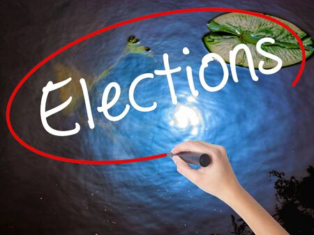 nomination: Woman Hand Writing Elections with marker over transparent board. Isolated on nature. Business concept. Stock Image Stock Photo