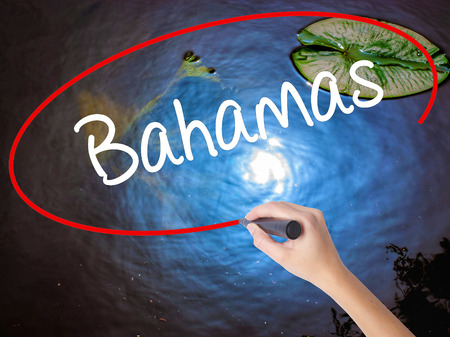 Woman Hand Writing Bahamas with marker over transparent board. Isolated on nature. Business concept. Stock Photo Stock Photo