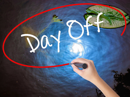 Woman Hand Writing Day Off  with marker over transparent board. Isolated on nature. Business concept. Stock Photo