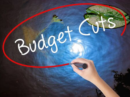 Woman Hand Writing Budget Cuts with marker over transparent board. Isolated on nature. Business concept. Stock Photo Stock Photo