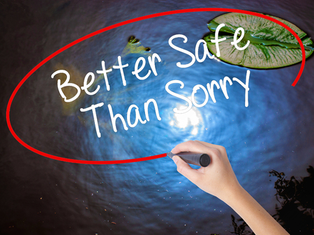 better safe than sorry: Woman Hand Writing Better Safe Than Sorry with marker over transparent board. Isolated on nature. Business concept. Stock Photo