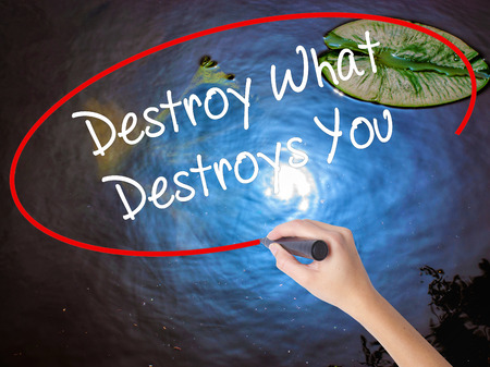 annihilate: Woman Hand Writing Destroy What Destroys You with marker over transparent board. Isolated on nature. Business concept. Stock Photo