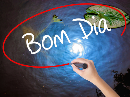 "Woman Hand Writing ""Bom Dia"" (In portuguese - Good Morning)  with marker over transparent board. Isolated on nature. Business concept. Stock Photo"