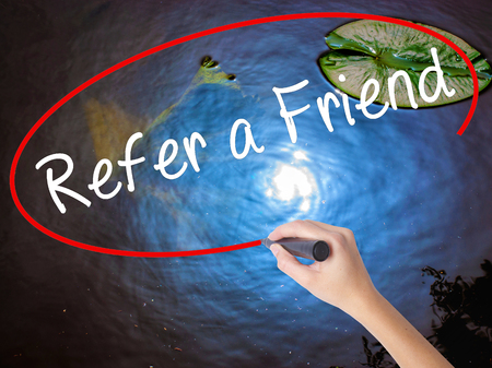 refer: Woman Hand Writing Refer a Friend  with marker over transparent board. Isolated on nature. Business concept. Stock Image Stock Photo