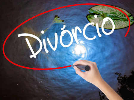 Woman Hand Writing Divorcio (Divorce in Portuguese) with marker over transparent board. Isolated on nature. Business concept. Stock Photo
