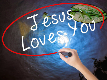 testament schreiben: Woman Hand Writing Jesus Loves You with marker over transparent board. Isolated on nature. Religion, technology, internet concept. Stock Image Lizenzfreie Bilder