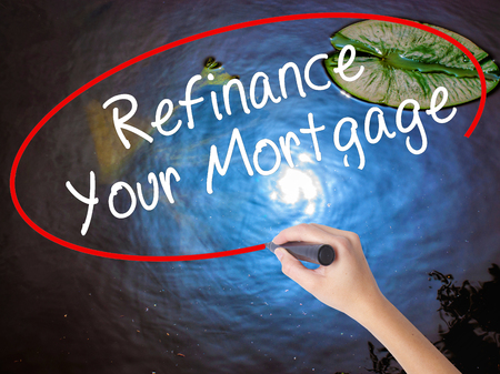 Woman Hand Writing Refinance Your Mortgage with marker over transparent board. Isolated on nature. Business concept. Stock Image Stock Photo