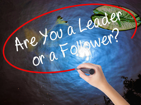 dutiful: Woman Hand Writing Are You a Leader or a Follower? with marker over transparent board. Isolated on nature. Business concept. Stock Photo