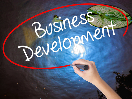 advise: Woman Hand Writing Business Development with marker over transparent board. Isolated on nature. Business concept. Stock Photo