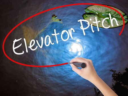 business pitch: Woman Hand Writing Elevator Pitch with marker over transparent board. Isolated on nature. Business concept. Stock Photo