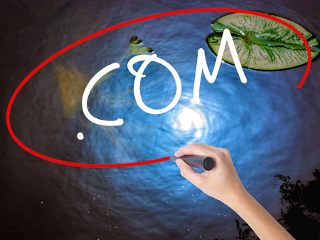 suffix: Woman Hand Writing .COM with marker over transparent board. Isolated on nature. Business concept. Stock Image