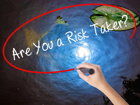 taker: Woman Hand Writing Are You a Risk Taker? with marker over transparent board. Isolated on nature. Business concept. Stock Photo