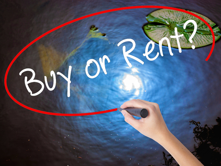 Woman Hand Writing Buy or Rent? with marker over transparent board. Isolated on nature. Business concept. Stock Image