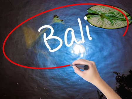 bali province: Woman Hand Writing Bali  with marker over transparent board. Isolated on nature. Business concept. Stock Photo