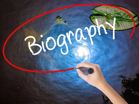 Woman Hand Writing Biography  with marker over transparent board. Isolated on nature. Business concept. Stock Photo