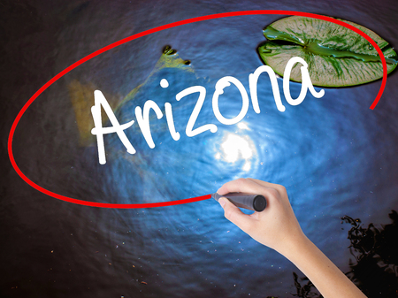 stone of destiny: Woman Hand Writing  Arizona  with marker over transparent board. Isolated on nature. Business concept. Stock Photo