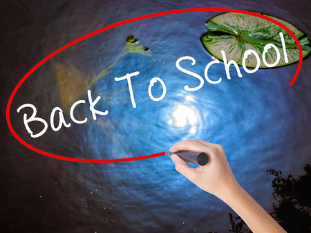 authors: Woman Hand Writing Back To School with marker over transparent board. Isolated on nature. Business concept. Stock Image Stock Photo