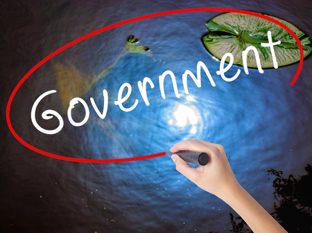 Woman Hand Writing Government with marker over transparent board. Isolated on nature. Business concept. Stock Image Stock Photo