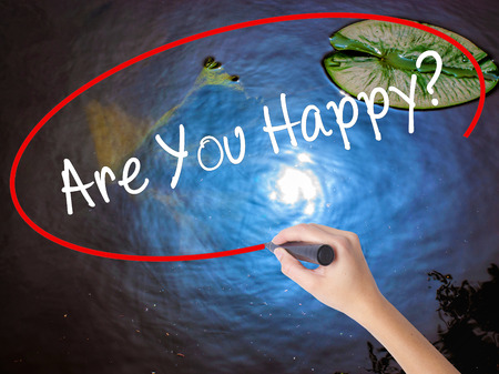 properous: Woman Hand Writing Are You Happy? with marker over transparent board. Isolated on nature. Business, technology, internet concept.