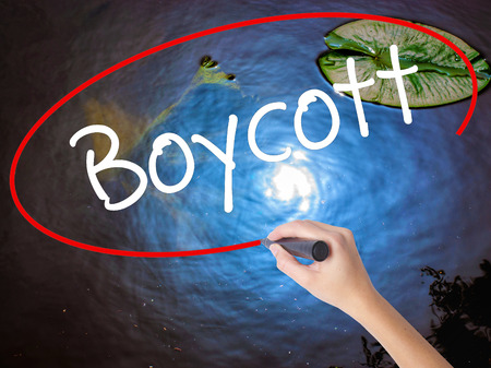 denying: Woman Hand Writing Boycott with marker over transparent board. Isolated on nature. Business concept. Stock Photo Stock Photo
