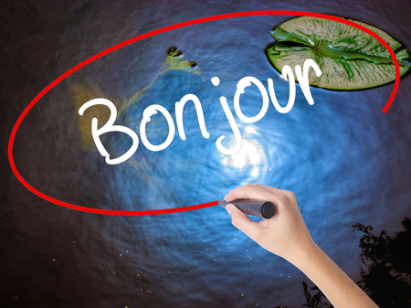 Woman Hand Writing Bonjour  (Good Morning in French) with marker over transparent board. Isolated on nature. Business concept. Stock Photo Stock Photo