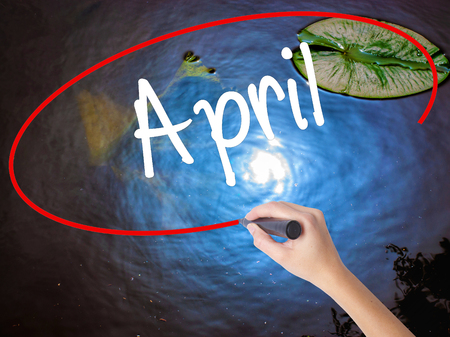 Woman Hand Writing  April  with marker over transparent board. Isolated on nature. Business concept. Stock Photo Stock Photo
