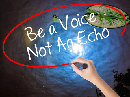 debating: Woman Hand Writing Be a Voice Not An Echo with marker over transparent board. Isolated on nature. Business concept. Stock Photo