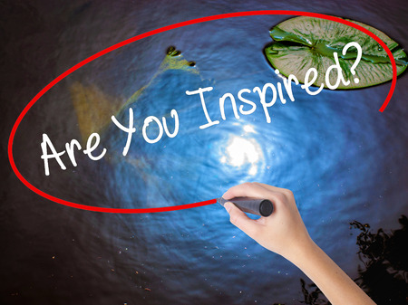 inspired: Woman Hand Writing Are You Inspired? with marker over transparent board. Isolated on nature. Business concept. Stock Photo Stock Photo