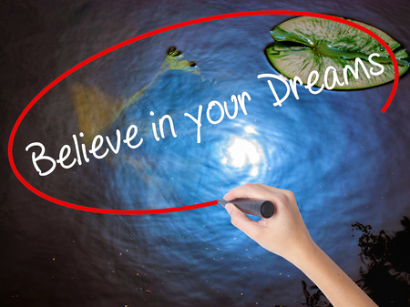 Woman Hand Writing Believe in your Dreams with marker over transparent board. Isolated on nature. Business concept. Stock Photo