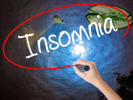 hallucinations: Woman Hand Writing Insomnia  with marker over transparent board. Isolated on nature. Business concept. Stock Photo