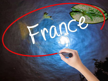 normandy: Woman Hand Writing France with marker over transparent board. Isolated on nature. Business concept. Stock Photo