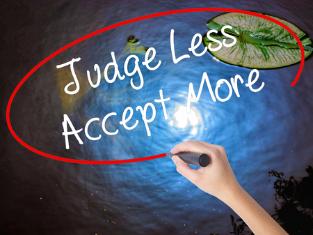 Woman Hand Writing Judge Less Accept More with marker over transparent board. Isolated on nature. Business concept. Stock Photo