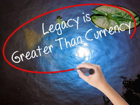 personal contribution: Woman Hand Writing Legacy is Greater Than Currency with marker over transparent board. Isolated on nature. Business concept. Stock Photo