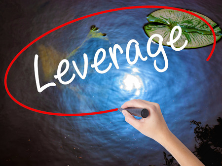 leverage: Woman Hand Writing Leverage with marker over transparent board. Isolated on nature. Business concept. Stock Photo