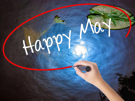 Woman Hand Writing Happy May with marker over transparent board. Isolated on nature. Business concept. Stock Photo