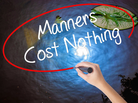 Woman Hand Writing Manners Cost Nothing with marker over transparent board. Isolated on nature. Business concept. Stock Photo