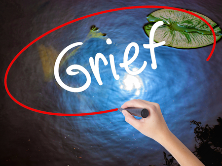 Woman Hand Writing Grief with marker over transparent board. Isolated on nature. Business concept. Stock Photo Stock Photo