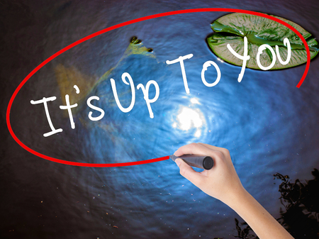 tasked: Woman Hand Writing Its Up To You with marker over transparent board. Isolated on nature. Business concept. Stock Photo