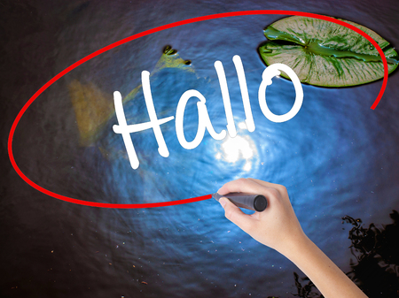 hallo: Woman Hand Writing Hallo  (Hello in German) with marker over transparent board. Isolated on nature. Business concept. Stock Photo