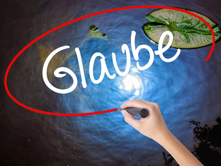 glaube: Woman Hand Writing Glaube (Believe in German) with marker over transparent board. Isolated on nature. Business concept. Stock Photo Stock Photo