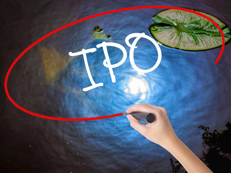valued: Woman Hand Writing IPO (Initial Public Offering)   with marker over transparent board. Isolated on nature. Business concept. Stock Photo