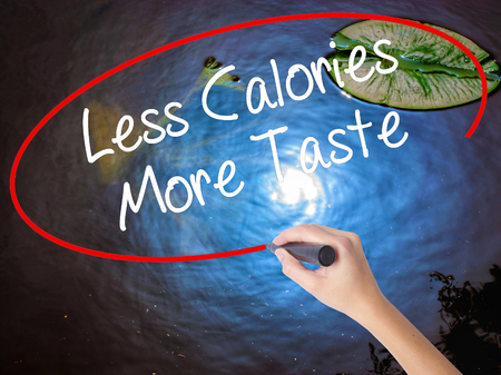 Woman Hand Writing Less Calories More Taste with marker over transparent board. Isolated on nature. Business concept. Stock Photo