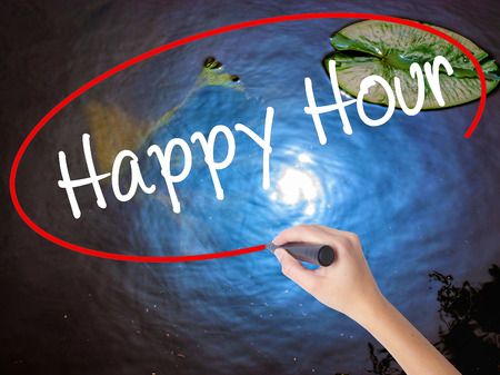 happyhour: Woman Hand Writing Happy Hour with marker over transparent board. Isolated on nature. Business concept. Stock Image