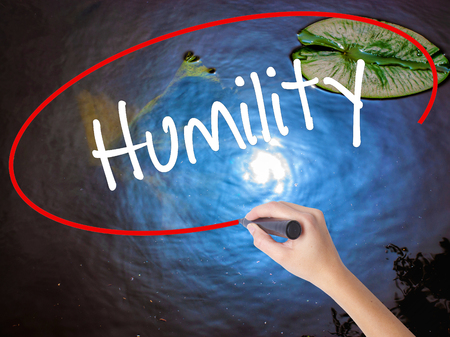 humility: Woman Hand Writing Humility  with marker over transparent board. Isolated on nature. Business concept. Stock Photo