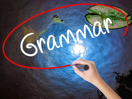 verb: Woman Hand Writing Grammar with marker over transparent board. Isolated on nature. Business concept. Stock Photo